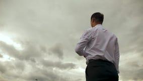 Ο επιχειρηματίας στο άσπρο πουκάμισο παίζει με το πετώντας αεροπλάνο εγγράφου στο κλίμα των σκοτεινών σύννεφων κίνηση αργή φιλμ μικρού μήκους