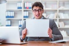 Ο επιχειρηματίας στο γραφείο που κρατά έναν κενό πίνακα μηνυμάτων Στοκ Εικόνες