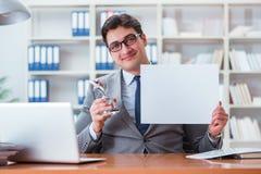 Ο επιχειρηματίας στο γραφείο που κρατά έναν κενό πίνακα μηνυμάτων Στοκ Φωτογραφία