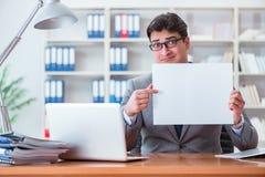 Ο επιχειρηματίας στο γραφείο που κρατά έναν κενό πίνακα μηνυμάτων Στοκ Εικόνα
