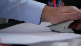 Ο επιχειρηματίας στο γραφείο που λειτουργεί με τα έγγραφα χρησιμοποιεί έναν Τύπο τρυπανιών για την παραγωγή των τρυπών φιλμ μικρού μήκους