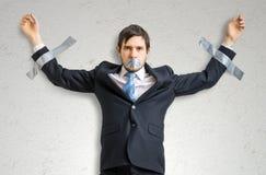 Ο επιχειρηματίας στο κοστούμι δένεται με ταινία στον τοίχο με την κολλητική ταινία Στοκ Φωτογραφία