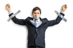 Ο επιχειρηματίας στο κοστούμι δένεται με ταινία στον τοίχο με την κολλητική ταινία Απομονωμένος στο λευκό Στοκ Εικόνες
