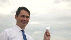 Ο επιχειρηματίας στο κοστούμι προωθεί το αεροπλάνο εγγράφου στον ουρανό και το χαμόγελο Επιχείρηση και ανάπτυξη Έννοια απόθεμα βίντεο