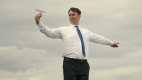 Ο επιχειρηματίας στο κοστούμι προωθεί το αεροπλάνο εγγράφου στον ουρανό και το χαμόγελο Τρελλά ενήλικα παιχνίδια παιδιών ατόμων π φιλμ μικρού μήκους