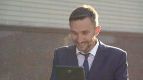 Ο επιχειρηματίας στο κοστούμι χρησιμοποιώντας την ταμπλέτα και εκφράζοντας τις συγκινήσεις κερδίζει 4K απόθεμα βίντεο