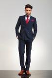 Ο επιχειρηματίας στο σταυρωτό κοστούμι που στέκεται με παραδίδει pock Στοκ Εικόνα