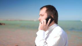 Ο επιχειρηματίας στο υπόβαθρο της όμορφης θάλασσας που μιλά στο τηλέφωνο, που λύνει τις περιπτώσεις απόθεμα βίντεο