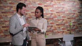 Ο επιχειρηματίας συζητά κάτι με την αμερικανική επιχειρηματία afro που κοιτάζει στον υπολογιστή ταμπλετών απόθεμα βίντεο