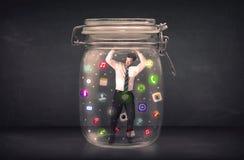 Ο επιχειρηματίας συνέλαβε σε ένα βάζο γυαλιού με τα ζωηρόχρωμα app εικονίδια con Στοκ φωτογραφία με δικαίωμα ελεύθερης χρήσης
