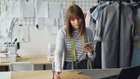 Ο επιχειρηματίας σχεδίου ιματισμού ελέγχει τα ράβοντας σχέδια εγγράφου και εξετάζει το smartphone Εξετάζει κάθε διακοπή απόθεμα βίντεο