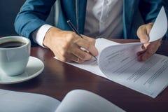 Ο επιχειρηματίας υπογράφει τα σημαντικά νομικά έγγραφα σχετικά με τον υπολογιστή γραφείου με το φλιτζάνι του καφέ στοκ εικόνα με δικαίωμα ελεύθερης χρήσης