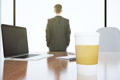 Ο επιχειρηματίας φαίνεται έξω το παράθυρο και το lap-top με το φλυτζάνι εγγράφου στο wo Στοκ Φωτογραφία