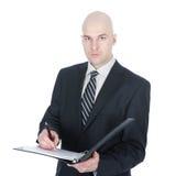 ο επιχειρηματίας φαίνεται σοβαρό γράψιμο σημειωματάριων Στοκ Εικόνες