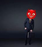 Ο επιχειρηματίας φορά το πρόσωπο smiley διαβόλων Στοκ εικόνες με δικαίωμα ελεύθερης χρήσης