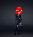 Ο επιχειρηματίας φορά το πρόσωπο smiley διαβόλων Στοκ φωτογραφία με δικαίωμα ελεύθερης χρήσης