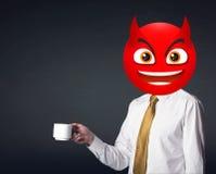Ο επιχειρηματίας φορά το πρόσωπο smiley διαβόλων Στοκ Φωτογραφίες