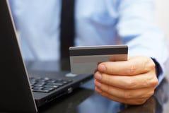 Ο επιχειρηματίας χρησιμοποιεί την πιστωτική κάρτα για τη σε απευθείας σύνδεση πληρωμή στο lap-top Στοκ Εικόνα