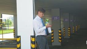 Ο επιχειρηματίας χρησιμοποιεί το τηλέφωνο στα πλαίσια ενός κενού υπαίθριου σταθμού αυτοκινήτων απόθεμα βίντεο