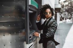 Ο επιχειρηματίας χρησιμοποιεί το ATM υπαίθρια στοκ φωτογραφία με δικαίωμα ελεύθερης χρήσης