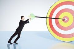 Ο επιχειρηματίας ωθεί το βέλος ακριβώς στην έννοια bullseye στοκ εικόνα με δικαίωμα ελεύθερης χρήσης