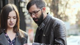 Ο επιχειρησιακοί άνδρας και η γυναίκα που στέκονται με τη συσκευή ταμπλετών στα χέρια στην οδό, μιλούν και που προσέχουν κάτι φιλμ μικρού μήκους