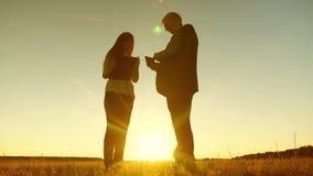 Ο επιχειρησιακός άνδρας με τη γυναίκα ταμπλετών και επιχειρήσεων με την ταμπλέτα συζητά το σχέδιο και το πρόγραμμα στο ηλιοβασίλε φιλμ μικρού μήκους