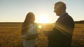 Ο επιχειρησιακός άνδρας με τη γυναίκα χαρτοφυλάκων και επιχειρήσεων με την ταμπλέτα διαπραγματεύεται στο ηλιοβασίλεμα και το γέλι φιλμ μικρού μήκους