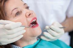 Ο επιδέξιος αρσενικός οδοντικός γιατρός συνεργάζεται με τον ασθενή στοκ φωτογραφίες