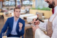 Ο επιδέξιος νέος σερβιτόρος λαμβάνει μια διαταγή Στοκ φωτογραφίες με δικαίωμα ελεύθερης χρήσης