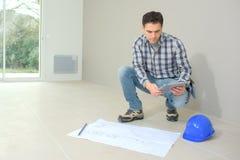Ο επόπτης κατασκευής ελέγχει το εσωτερικό εργοτάξιο οικοδομής Στοκ Εικόνες