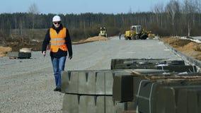 Ο επόπτης μηχανικών ελέγχει τη διαδικασία εργασίας του οδικού κτηρίου πρίν βάζει της συγκράτησης ή roadbed πεζοδρομίων από βαρύ φιλμ μικρού μήκους
