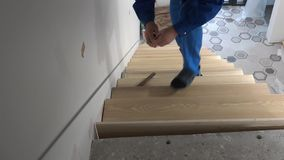 Ο ερασιτέχνης εργαζόμενος τοποθετεί το δρύινο βήμα σκαλοπατιών στη σκάλα και το μέτρο με το εργαλείο μετρητών απόθεμα βίντεο