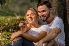 Ο εραστής κάθεται μαζί δημόσια το πάρκο δείχνοντας το δάχτυλο κάτι που ενδιαφέρει με το ευτυχές χαμόγελο στοκ φωτογραφία