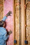 Ο εργάτης οικοδομών βάζει επάνω κάποια μόνωση μεταξύ των στηριγμάτων Στοκ Εικόνες