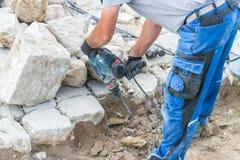 Ο εργάτης οικοδομών εργάζεται με τις πέτρες γρανίτη Στοκ εικόνα με δικαίωμα ελεύθερης χρήσης