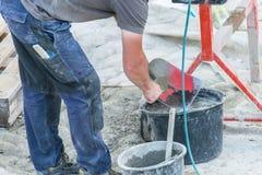 Ο εργάτης οικοδομών καθαρίζει ένα φτυάρι Στοκ Εικόνες