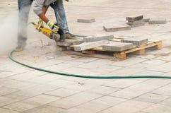 Ο εργάτης οικοδομών κόβει τη συγκράτηση διάβασης πεζών με το κυκλικό πριόνι Το άτομο προστατεύει την ακρόαση από τους κινδύνους θ στοκ εικόνες
