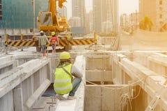 Ο εργάτης οικοδομών στο πράσινο γιλέκο και το κίτρινο κράνος και ο Μαύρος καλύπτουν να γονατίσουν κάτω στην ακτίνα χάλυβα στοκ φωτογραφίες