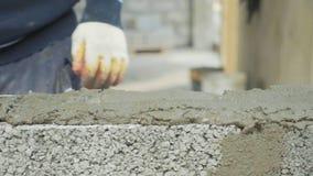 Ο εργάτης οικοδομών χτίζει το τουβλότοιχο, άποψη κινηματογραφήσεων σε πρώτο πλάνο στο εργοτάξιο οικοδομής φιλμ μικρού μήκους