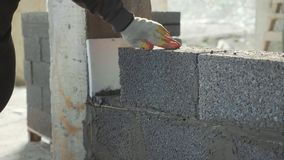 Ο εργάτης οικοδομών χτίζει το τουβλότοιχο, άποψη κινηματογραφήσεων σε πρώτο πλάνο στο εργοτάξιο οικοδομής απόθεμα βίντεο