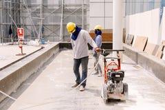 Ο εργάτης οικοδομών έκοβε oncrete στη ζώνη κατασκευής Στοκ Φωτογραφία