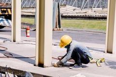 Ο εργάτης οικοδομών ήταν ήμερος χάλυβας στη ζώνη κατασκευής Στοκ Φωτογραφίες