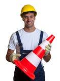 Ο εργάτης οικοδομών εξασφαλίζει ασφάλεια σε ένα άσπρο υπόβαθρο Στοκ Εικόνα