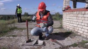 Ο εργάτης οικοδομών διαιρεί το τούβλο με το σφυρί απόθεμα βίντεο