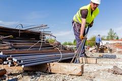 Ο εργάτης οικοδομών παίρνει armature ενίσχυσης από το σωρό, Bu Στοκ εικόνα με δικαίωμα ελεύθερης χρήσης
