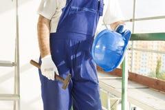 Ο εργάτης οικοδομών σε μια ενδυμασία εργασίας, προστατευτικά γάντια κρατά ένα κράνος και ένα σφυρί Εργασία στο μεγάλο υψόμετρο Υλ Στοκ φωτογραφίες με δικαίωμα ελεύθερης χρήσης
