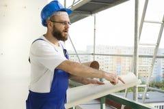 Ο εργάτης οικοδομών σε μια εξάρτηση εργασίας και σε ένα κράνος στέκεται σε ένα μεγάλο υψόμετρο σε ένα εργοτάξιο οικοδομής με τα σ Στοκ φωτογραφία με δικαίωμα ελεύθερης χρήσης
