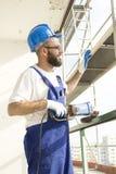 Ο εργάτης οικοδομών στη λειτουργώντας εξάρτηση και στο προστατευτικό κράνος στέκεται στο μεγάλο υψόμετρο στο εργοτάξιο οικοδομής Στοκ Εικόνες