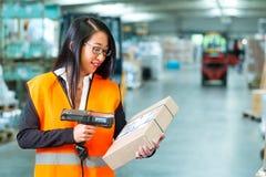 Ο εργαζόμενος ανιχνεύει τη συσκευασία στην αποθήκη εμπορευμάτων της αποστολής στοκ εικόνες με δικαίωμα ελεύθερης χρήσης